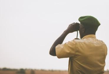 park ranger looking through binoculars